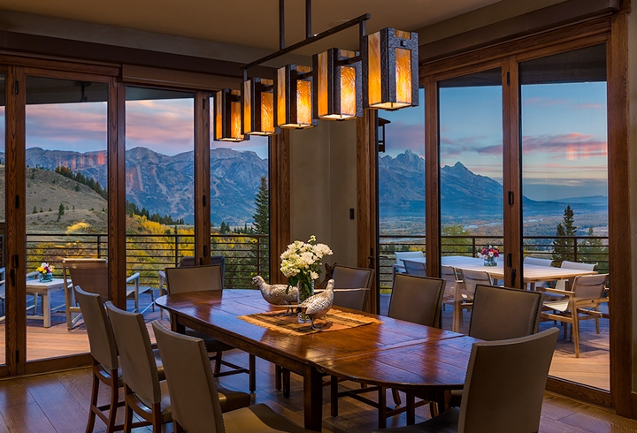 A custom Hammerton contemporary dining light in dark art glass and hammered steel enhances the sweeping postcard view of this Wyoming dining room | Trynity DeVries Interior Design | Bozeman, MT